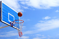 Basketball scoring a goal through the net. On blue sky background royalty free stock photo