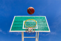 Basketball scoring goal on yellow hoop. With blue sky background royalty free stock photography
