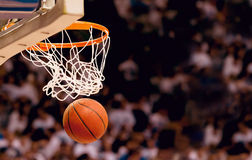 Basketball Scoring Points. An action photo of a basketball going through the basket of a live game. Scoring points