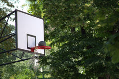 Basketball Scoring Points. An action photo of a basketball going through the ragged basket hoop of a street game. Scoring points in green park settings Stock Photo