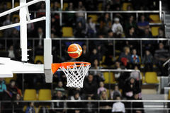 Basketball scoring in the stadium. Basketball scoring during match in arena. Basketball hoop on supporters background Royalty Free Stock Images