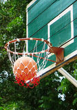 Basketball. Shooting Basketball through the basket at a sports arena Royalty Free Stock Photos