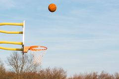 Basketball shot, midair. Basket ball shot and mid air capture on a bright day. The basket net is left of frame with room space for copy stock images