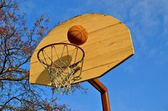 Basketball sits on an old rim and backboard Stock Images