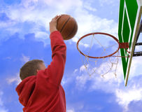 Basketball slam dunk. Young boy making basketball shot dunk on blue sky and white clouds backgrounds Stock Photo
