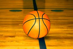 Basketball Solidarity. A basketball sits at midcourt awaiting the start of a high school ball game royalty free stock images