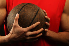 Basketball-Spieler, der Kugel anhält Stockfotografie