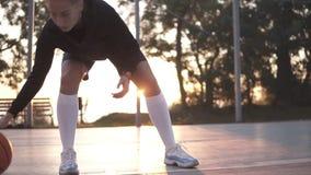 Basketball-Spieler des jungen Mädchens, der auf Gericht im Freien trainiert Den Ball auf dem Knöchelniveau niedrig aufprallen, üb stock video