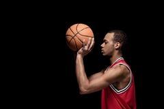 Basketball-Spieler des jungen Mannes mit Ball auf Schwarzem Lizenzfreie Stockfotos