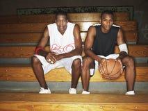 Basketball-Spieler, die auf Bank sitzen Lizenzfreie Stockbilder