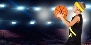 Basketball-Spieler mit Ball in der Turnhalle Kleine Schritte in einem großen Basketball stockfotos