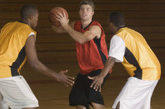 Basketball-Spieler mit dem Ball, der von den Gegnern blockiert wird Stockfotografie