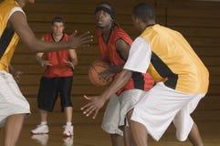 Basketball-Spieler mit dem Ball, der von den Gegnern blockiert wird Lizenzfreies Stockfoto