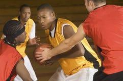 Basketball-Spieler mit dem Ball, der von den Gegnern blockiert wird Stockfoto