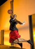 Basketball-Spieler springt mit Kugel Stockfotos