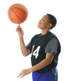 Basketball Spinner. A preteen boy happily spinning his basketball on his index finger. Motion blur on the ball, On a white background Royalty Free Stock Image