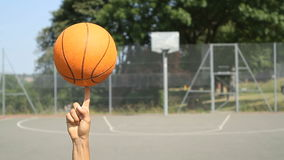 Basketball spinning on a finger on an outdoor court stock video footage