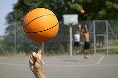 Basketball Spinning. Spinning Basketball in foreground with blurred players in the background Stock Photo