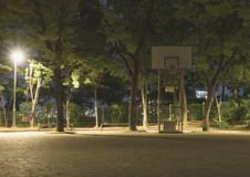 A basketball stand and a lay of light from streetlamp in an outdoor playground in the night stock photo