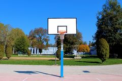 Basketball structure in an outdoor playground surrounded by trees Stock Image