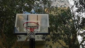 Basketball structure rim in an outdoor backyard playground surrounded by trees.  stock video