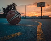 Basketball with sunset in the background stock images