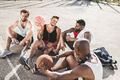 Basketball team sitting after game on basketball court together. Multiethnic basketball team sitting after game on basketball court together royalty free stock image