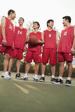 Basketball team standing and smiling, portrait Royalty Free Stock Photo