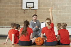 Basketball-Team Trainer-Giving Team Talk To Elementary School Stockfotos
