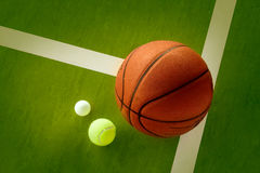 A basketball, a tennis ball and a Ping-Pong ball. On the green background Stock Photo