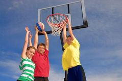 Basketball time. Father plays basketball with teens Stock Photos