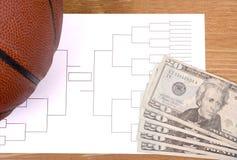 March Madness Basketball Bracket and Fanned Money. A basketball, tournament bracket and twenty dollar bills stock image