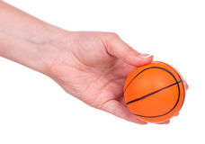 Basketball toy ball. Small basketball toy ball in female hand over white background Stock Photography