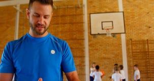 Basketball-Trainer, der in der Schule digitale Tablette im Basketballplatz 4k verwendet stock video