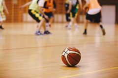 Basketball Training Game Background. Basketball on Wooden Court Floor. Close Up with Blurred Players Playing Basketball Game in the Background royalty free stock images