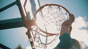 A basketball training outside. Throwing a ball in a basketball hoop. The ball gets right in target. View from the bottom stock video footage