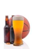 Basketball und zwei Bierflaschen und Glas Stockbild