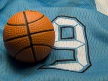 Basketball uniform and ball. Small ball on the number nine uniform Royalty Free Stock Photos