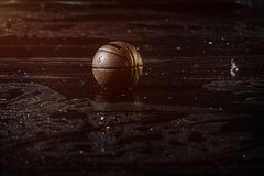 Basketball on wet Court Floor close up with blurred background. Under the rain. Stock Image