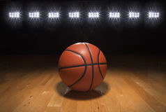 Basketball on wood floor beneath bright lights