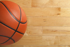 Basketball on wood gym floor viewed from above Royalty Free Stock Photos