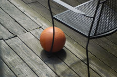 Basketball on wooden deck. A basketball awaits use on a weathered wooden deck by a chair leg stock images