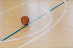 Basketballball über Boden in der Turnhalle lizenzfreies stockbild