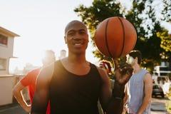 Basketballkerle, die auf die Straße spielt mit dem Ball gehen lizenzfreie stockbilder