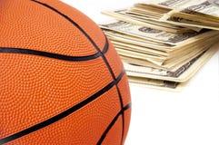 Basketballkugel auf Hintergrund der Dollar. Lizenzfreies Stockfoto