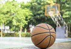 Basketballleder auf dem Holzstuhl mit Wassertröpfchen Hintergrundbasketballplatz und -park stockbilder