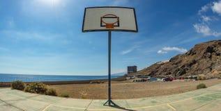 Basketballrückenbrett mit Korb auf dem alten Sportfeld Enormes verlassenes Gebäude vor dem Ozean im weiten Hintergrund lizenzfreie stockfotografie