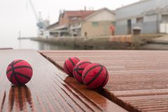Four red basketballs on the panels of the harbor dull day stock photography