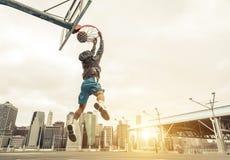 Basketballstraßenspieler, der einen hinteren Slam Dunk macht Lizenzfreie Stockfotos