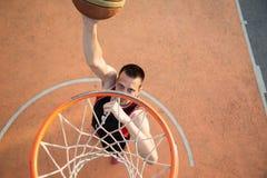 Basketballstraßenspieler, der einen Slam Dunk macht Lizenzfreie Stockfotografie